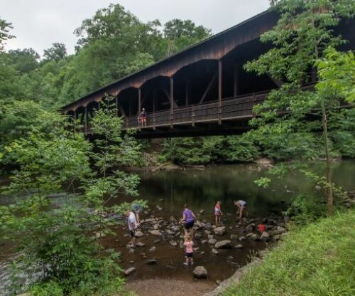 Family exploring underneath covered bridge