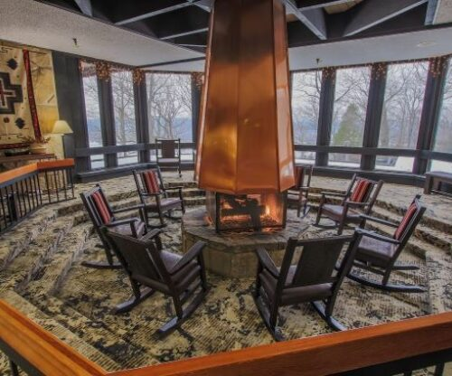 Chairs setup around the central fireplace of the main lodge