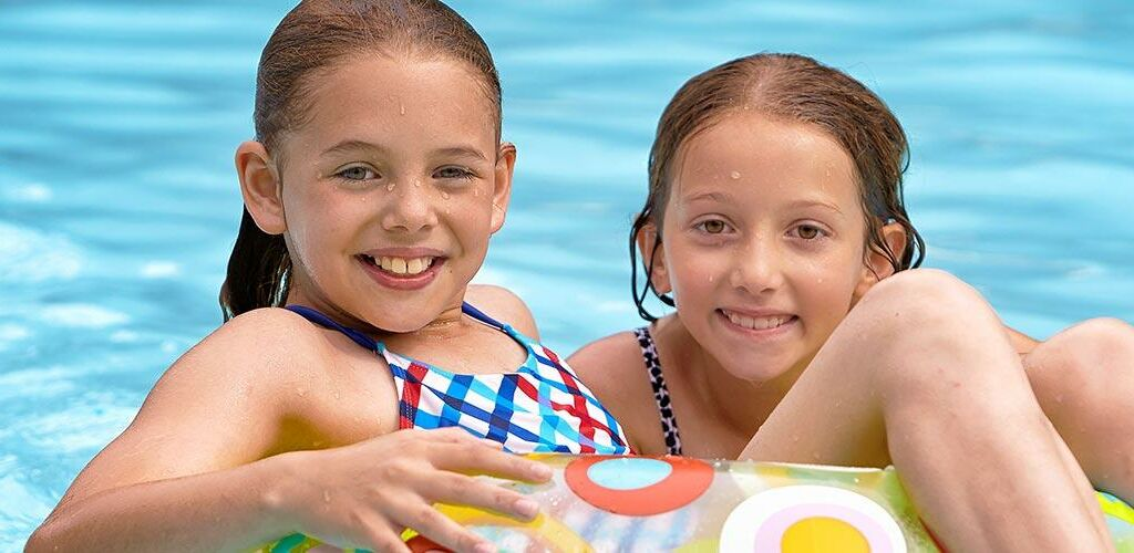 Two girls playing in the pool on a floaty